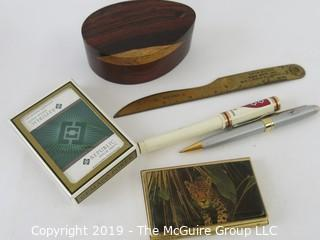 WYSIWYG: Desktop items: wood oval box, playing cards, letter opener, Harvard pen, Jaguar card case, pen