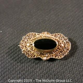 Jewelry:  Antique design, oval 14K yellow gold filigree with bezel set black onyx brooch, 32 x 18 mm.  Like new. 4.3 grams total weight; (TMG 756)