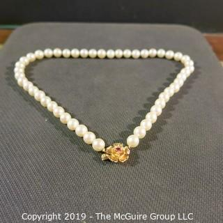Jewelry: Lovely, knotted 15 in. strand of 7mm, white, Akoya pearls with 14K Yellow gold floral clasp with safety, and center 2.5 mm ruby. (TMG 757)