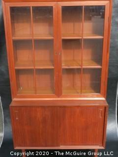 Danish Mid Century Stepped Back glass front cabinet; two doors over two sliding doors; base is 36W x 28T x 17D; top is 36W x 36T x 13D