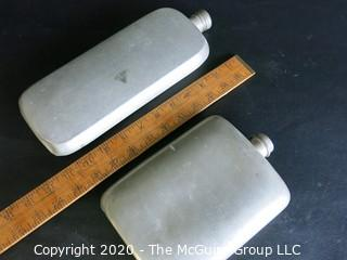 "Two Metal Flasks.  Measures approximately 11"" and 9"" tall.  As is, one missing top."