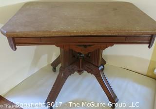 "Marble top side table on carved base with castors; 17 1/2 x 25 x 19 1/2""T"