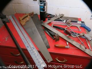 Collection of tools including bar clamps, metal rulers, square, hand saws, hand drill, hack saw, scroll saw