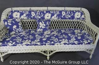 Antique Wicker Settee Sofa or Couch with Blue and White Cushions.
