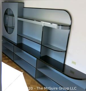 "Reproduction Art Deco Style Shelving Unit. Made of Grey Laminate with Wood Substrate. Top shelf has built in lighting. Designed to resemble display shelves of the Chase giftware department at many prominent retailers in the 1930's, including Gimbels. 168"" wide x 91""T"