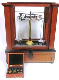 "Antique Triple Beam Balance Gold or Apothecary Cabinet Scale in a Glass and Wood Case Made by Voland & Sons of New Rochelle, NY, 1912. It has glass panels on all four side and has one drawer with box of scale weights. It measures approximately 21"" x 16"" x 9""."