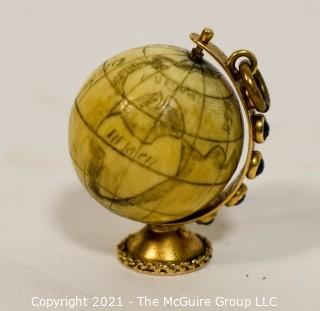 "Antique Scrimshaw Articulated Globe Charm or Pendant in 14kt Gold Stand with Raw Sapphire Decorative Gemstones. It measures approximately 1 1/4"" tall and weights 10.7g."
