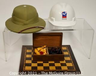 Collection including chess board with wooden pieces, Pentagon Renovation Program Hard Hat and Singaporean Field Hard Hat.