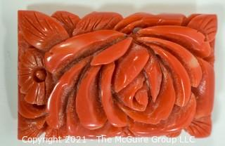 "Molded Red Celluloid or Bakelite Clip, Made in Japan. It measures approximately 2"" long and 1 1/4"" wide."