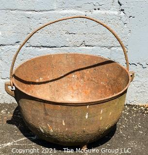 """Large Tri-footed Cast Iron Cauldron with Handle.  Drain slot in Base.  Measures 24""""D x 14""""H."""