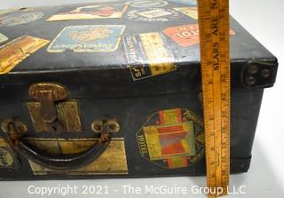 """Vintage Fiberglass Drum Case Covered in International Luggage Travel Labels and Tags.  Measures 9"""" D x 17""""W x  24""""L."""
