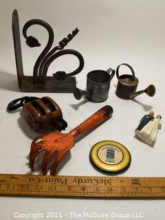 Group of Metal and Outdoor Items Including Cast Iron Bracket, Two (2) Miniature Watering Cans, Orange Garden Trowel, Vintage Anvil Brand Two-Strand Pully, Cake Topper Bride & Groom and Morton Salt Hand Mirror.
