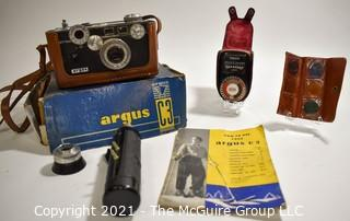 Untested Argus C3 35mm Rangefinder Film Camera with Leather Case in Original Box with Paperwork; Polyco Light Meter and Set of Color Correcting Lenses in Case.  Box is in worn condition.