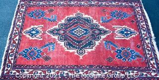 """Hand Woven Persian Rug on Red Background. Measures approximately 60"""" x 89""""."""