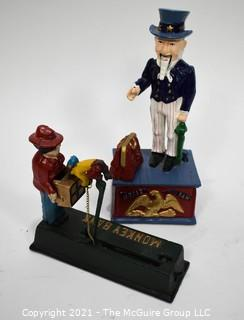 Two (2) Reproduction Cast Iron Mecanical Banks - Uncle Sam and Monkey Bank.