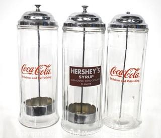 Three (3) Glass & Chrome Soda Fountain Straw Dispensers with Coca Cola & Hershey Logos