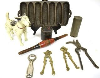Collection of Primitive Tools.  Includes Terrier Dog Cast Iron Door Stop, Painted Naan Roller, Ware Cast Iron Corn Bread Pan, Tole Painted Tin, Nutmeg Grater, LaBatt's Bottle Opener, (2) Brass Nutcrackers & French Vineyard Shears.  {Note: Description Altered 10.14.2021 @ 6:46pm ET}
