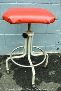 Industrial Adjustible Tubular Steel Rolling Stool with Red Vinyl Seat.
