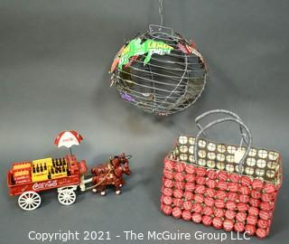Three Decorative Items Including Coca - Cola Cast Iron Delivery Wagon With Driver, Horses and Crates, Tote Made of Bottle Caps & Wire Folk Art World Globe.