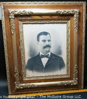 Framed black and white male portrait studio photo mounted in antique wood frame