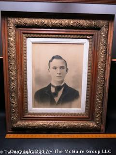 Studio photograph of a young man in antique wooden art frame