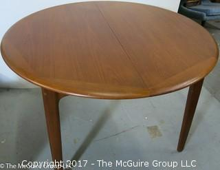"Danish M-C Modern teak dining table and matching chairs (5 side; 1 arm) ; table expands; with leaves stored on the underside, as shown; 45""D x 28 1/2"" T"