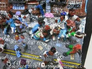 """Willie Mays signed montage by Diane Marie Cobert Brunner; depicts street scene in Harlem where Mays was a popular figure participating in local stickball games, where it was said that in the urban game of hitting a rubber ball with an adapted broomstick handle, Mays could hit a shot """"six sewers"""" (6 consecutive New York City manhole covers, nearly 300 feet).  A note card (lower right) says: """"In 1950 when the Giants signed me, they gave me $15,000.  I bought a 1950 Mercury.  I couldn't drive, but I had it in the parking lot there, and everybody that could drive would drive the car, so it was like a community """"thing"""" - Willie Mays""""    The artist has exhibited her works at the Empire State Building, the Museum of Contemporary Art in San Diego, the Yogi Berra Museum in New Jersey and the Museum of the Living Artist in San Diego. 21 1/2""""W x 26 1/2""""T x 7 1/2""""D {comes with custom made clear plexiglass cover} Description altered Dec. 6 at 9:54am ET"""