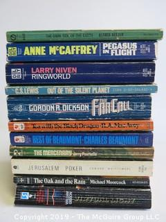 Collection of books including authors Rester, McCaffrey, Niven, C.S. Lewis, Dickson, MacAvoy, Beaumont, Pournelle, Moorcock, and Gibson