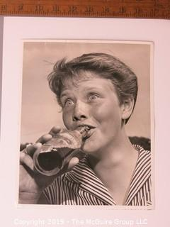 Photo: Historical; Americana: Golf: Identified expressive girl drinking soda